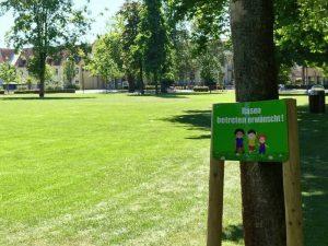 Ein Schild mit dem Hinweis, Rasen betreten erwünscht